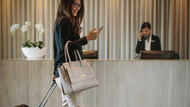 A woman on her phone carrying luggage through a hotel.