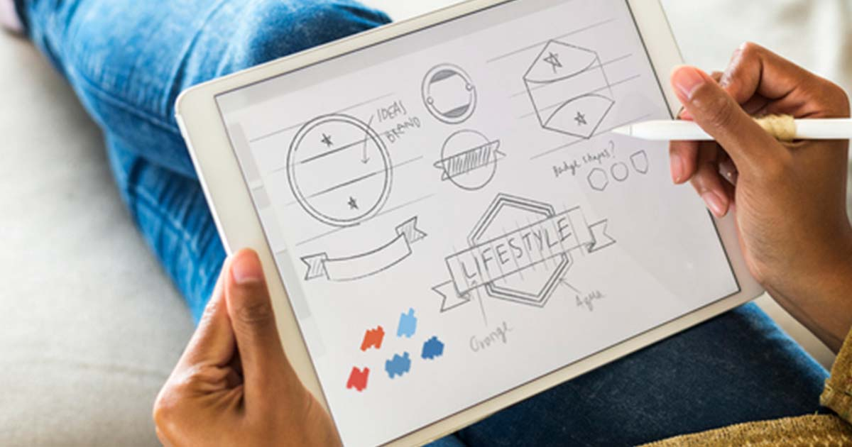 An entrepreneur sketching logos for their brand on a tablet.