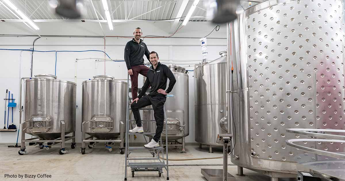 Founders of Bizzy Coffee posing next to cold brew equipment.