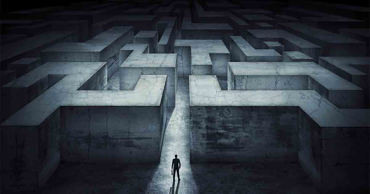 A man standing before a massive maze