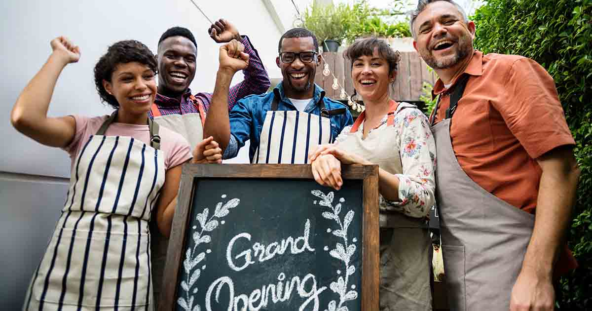 Group of new business owners behind their grand opening sign.