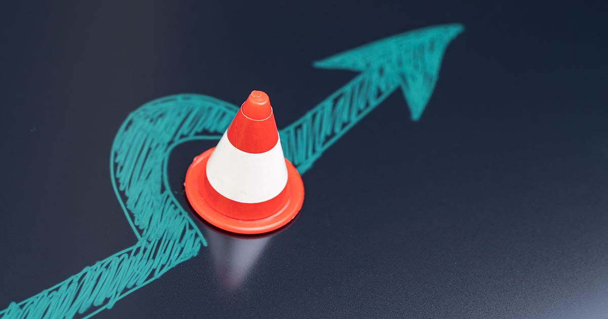 Chalk drawing of arrow avoiding traffic cone obstacle.