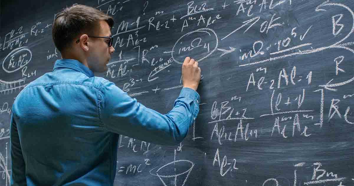 Man writing on chalkboard.