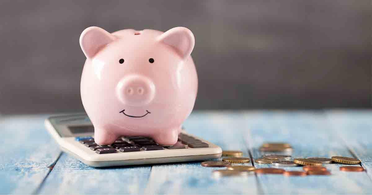Piggy bank on a calculator next to coins.