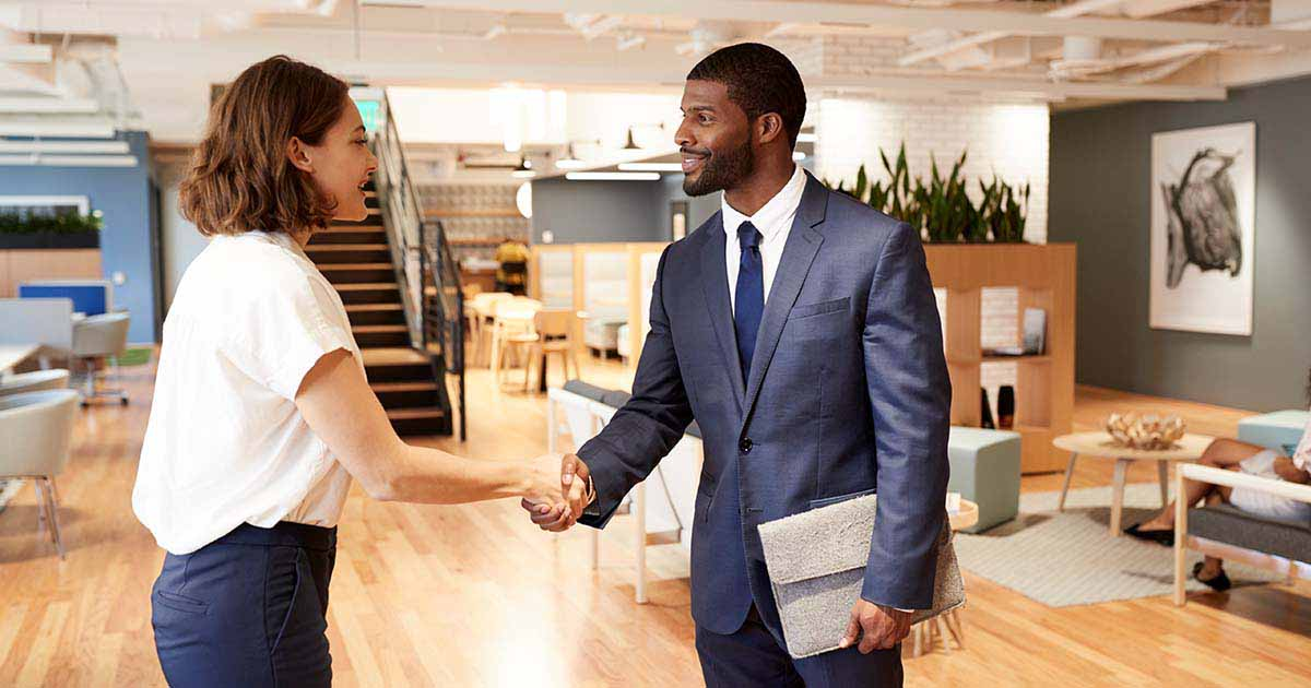 A woman and a man shaking hands before an interview.