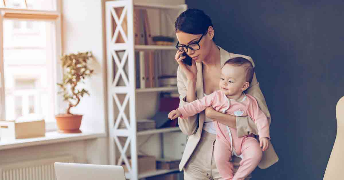 Woman entrepreneur working and holding her child.