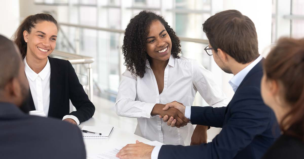 Businesswoman shaking hands with businessman.