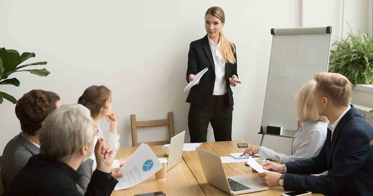 Woman business owner in suit presenting to her team.