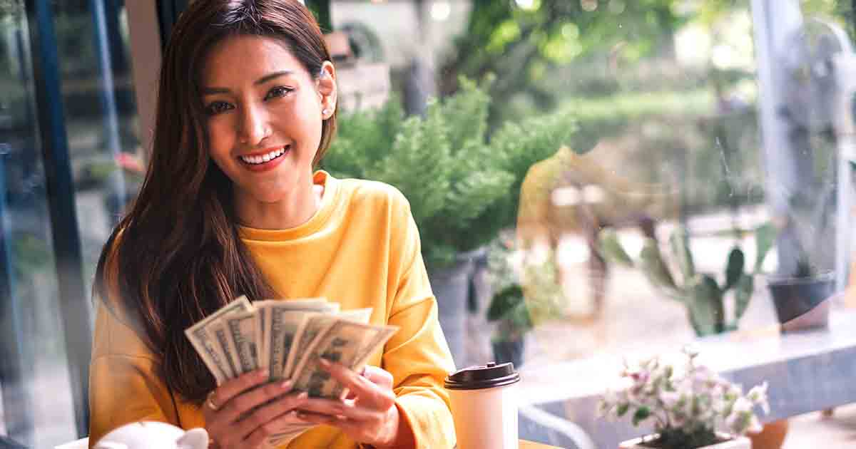 Smiling woman holding money.