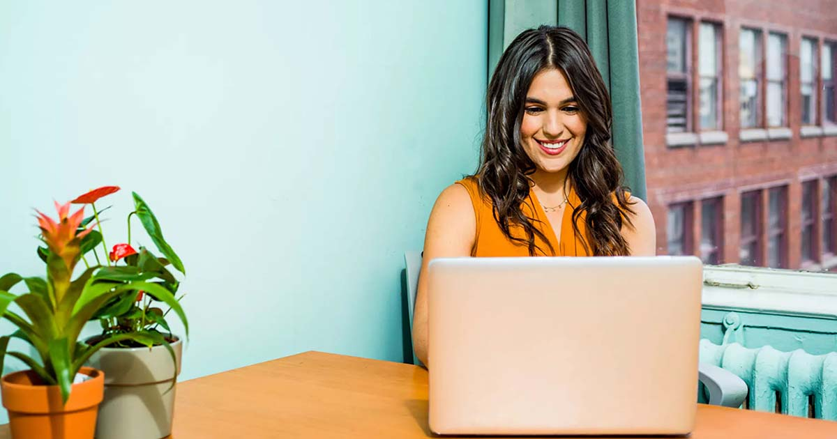 Woman smiling while taking a digital course online.