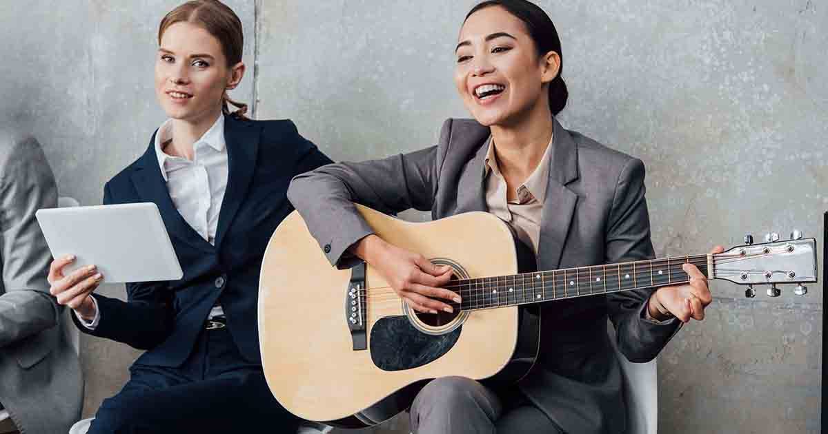 Two women in business suits laughing and playing the guitar.