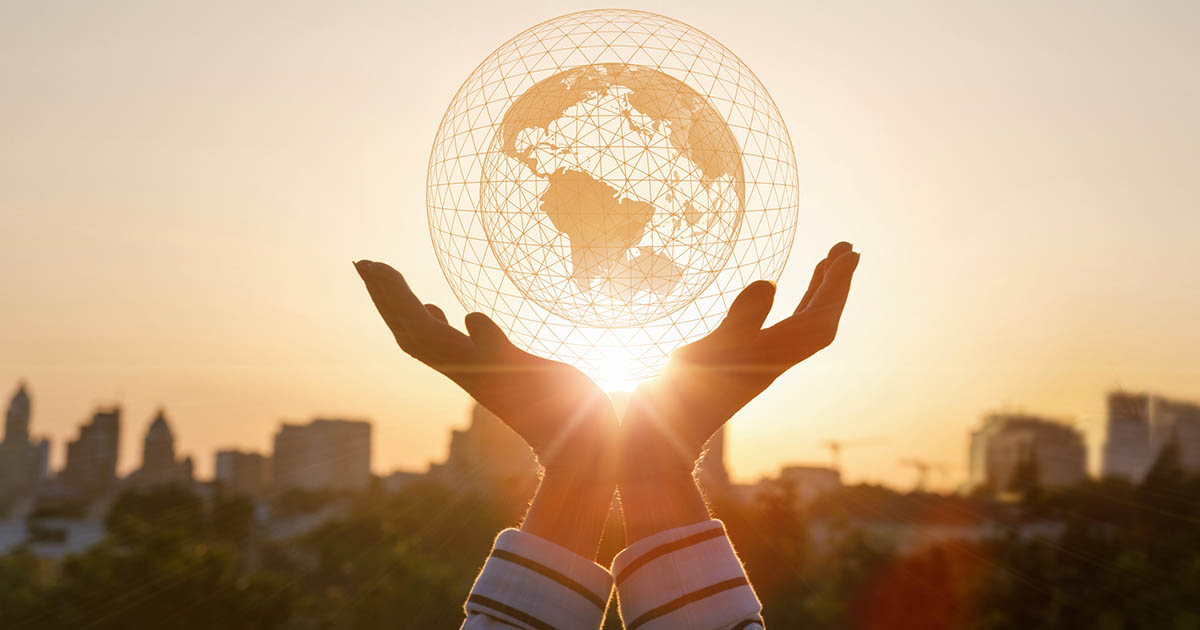 Woman's hands holding the world with sunlight shining through
