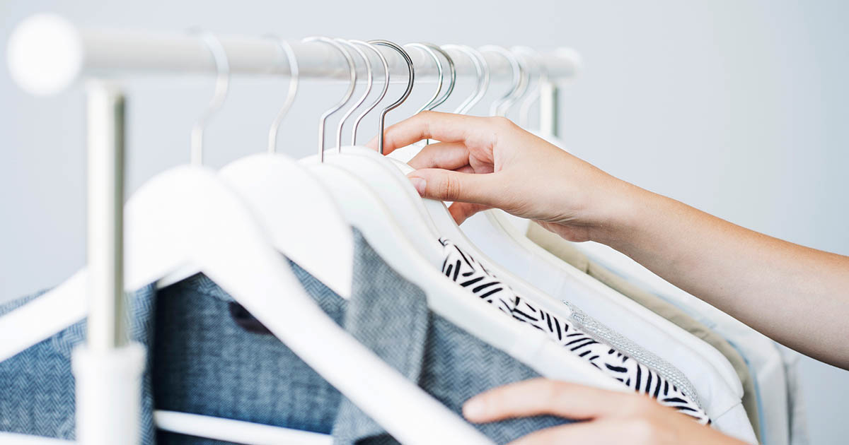 A rolling rack with professional work apparel on white hangers.