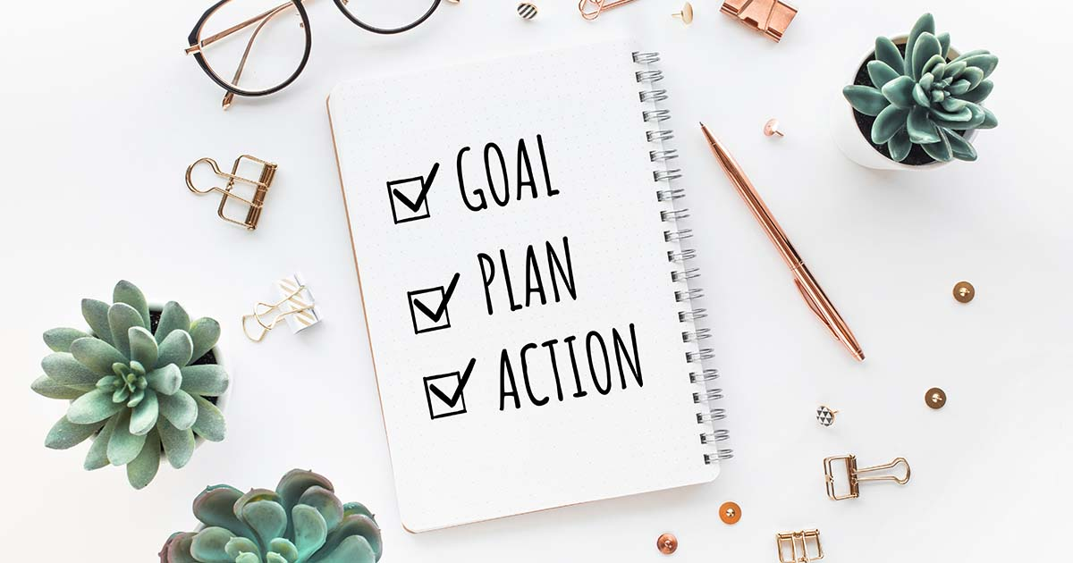 """Notepad stating, """"Goal, Plan, Action"""" and various office accessories."""
