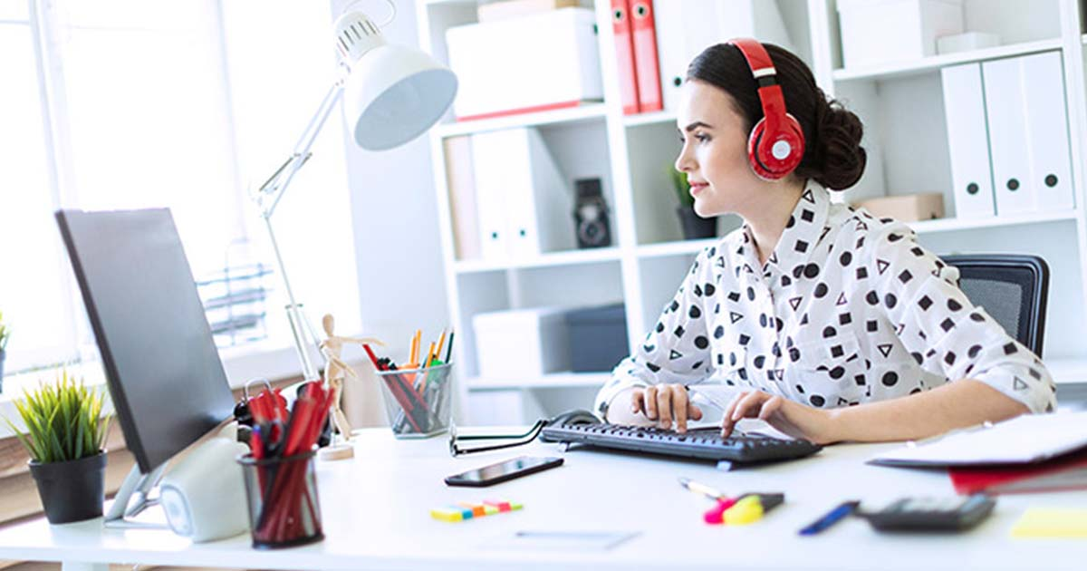 Smiling woman at desk working at computer with headphones