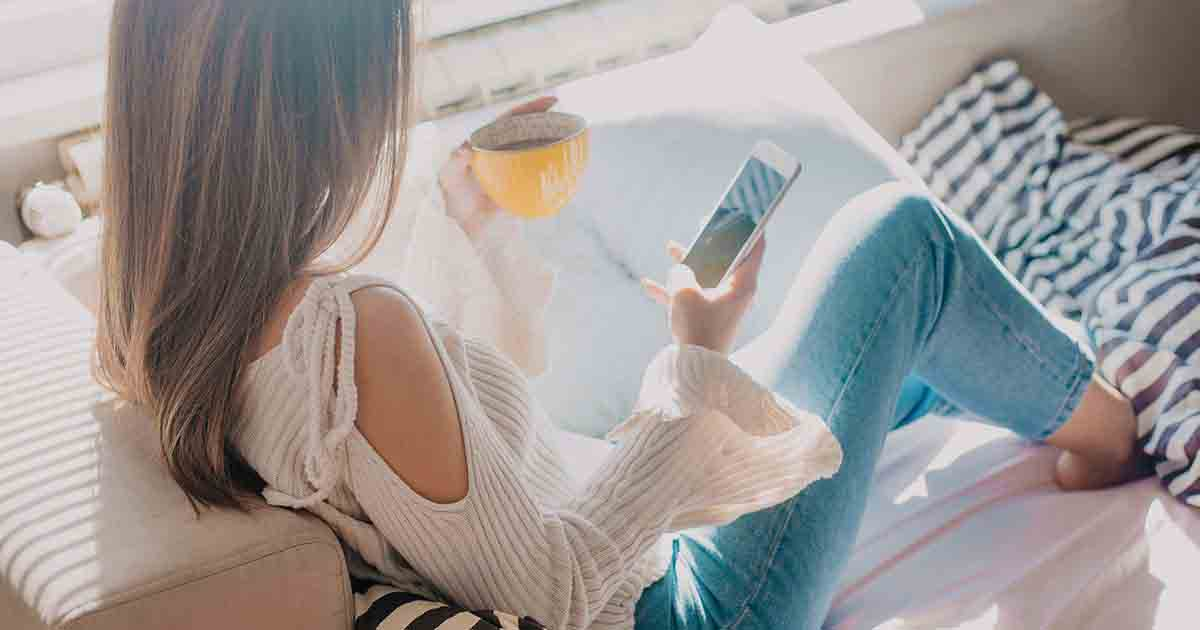 Woman relaxing on a couch looking at self-care apps on her phone.